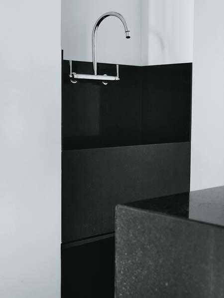 Como a lavanderia fica integrada à cozinha, o tanque de granito preto são g...
