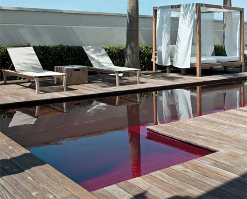 Inteira vermelha, a piscina tem mosaicos de vidro (ref. 3950, Vidrotil) e rej...