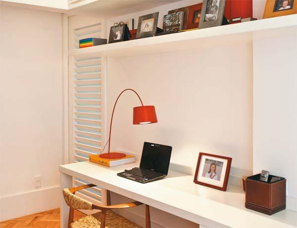 Escritório com bancada, estante e armário.