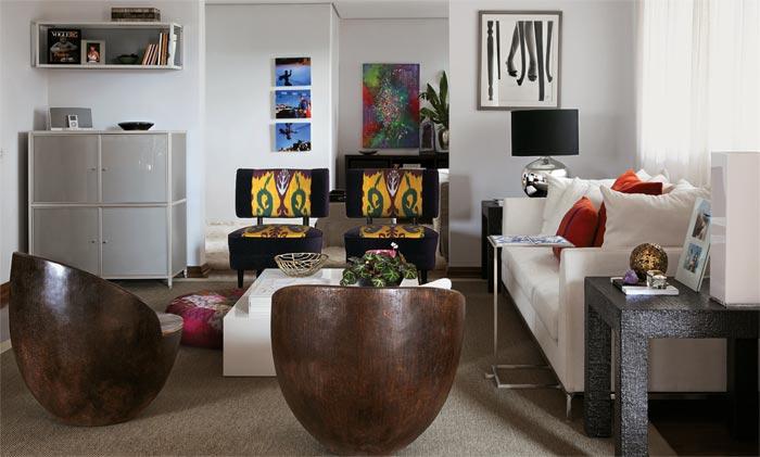 Almofadas laranja, produzidas em Minas Gerais, avivam o sofá de camurça sin...