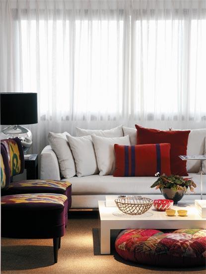 Almofadas, poltronas e um pufe indiano compõe a sala com estilo indiano