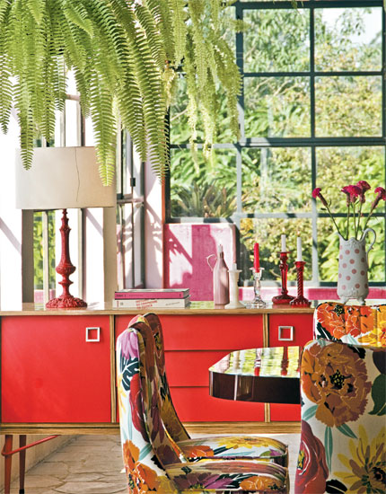 Na sala de jantar, a dupla vermelho e fúcsia se repete em diferentes nuances...
