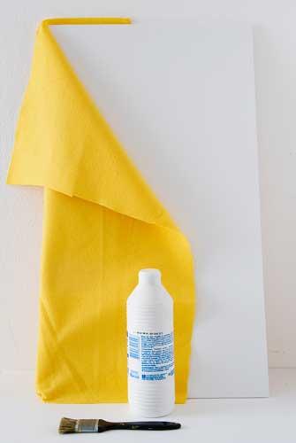 Usando a trincha, passe a cola na base do mural e aplique o feltro cobrindo t...