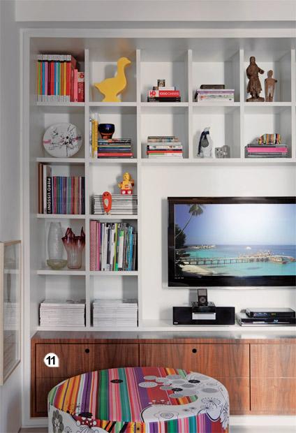 11. Encaixadas sob a estante da TV, gavetas de nogueira ocultam CDs, DVDs e a...
