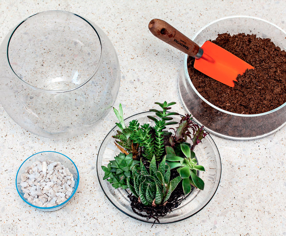 Aquário redondo de vidro vazio, pote com pedrinhas, pote com planta, e um pote com terra e uma pá de jardinagem laranja