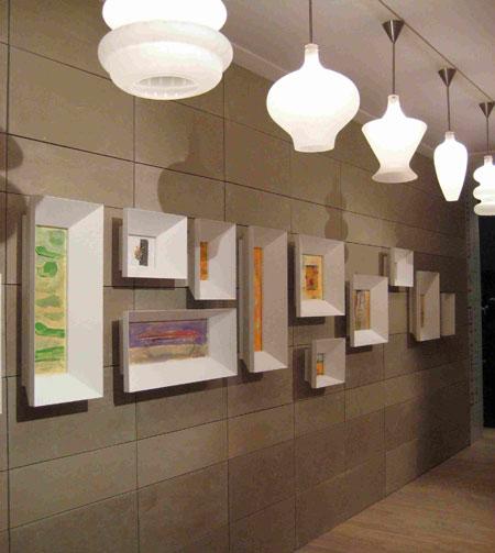 No corredor, coleção de quadros com molduras volumosas e uma série de lumi...