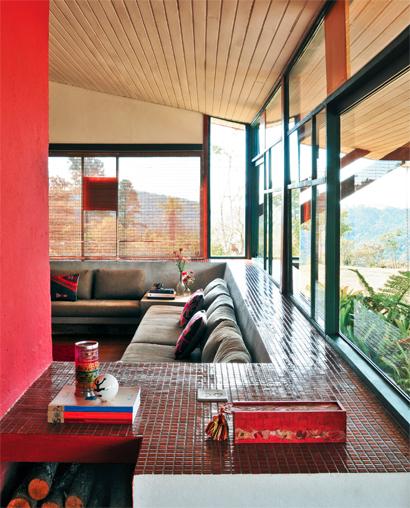 Embora toda envidraçada e aberta para a paisagem, a sala também passa a sen...