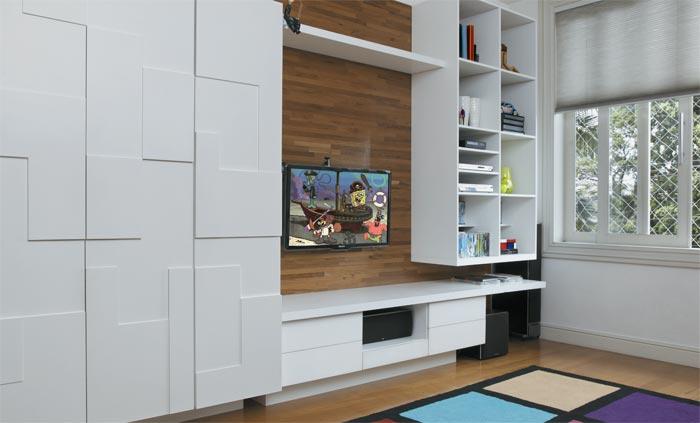 O armário laqueado divide a mesma parede com um painel de freijó com nichos...