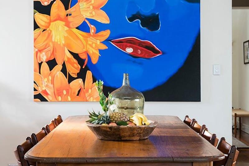 sala-de-jantar-com-mesa-baixa-de-madeira-e-quadro-impactante