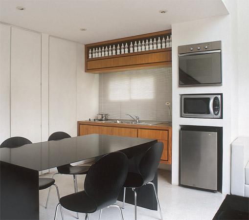 Na cozinha integrada à área social, os eletrodomésticos ficam embutidos em...
