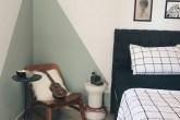 cama com conjunto quadriculado branco e preto e parede rosa claro com formas triangulares verde