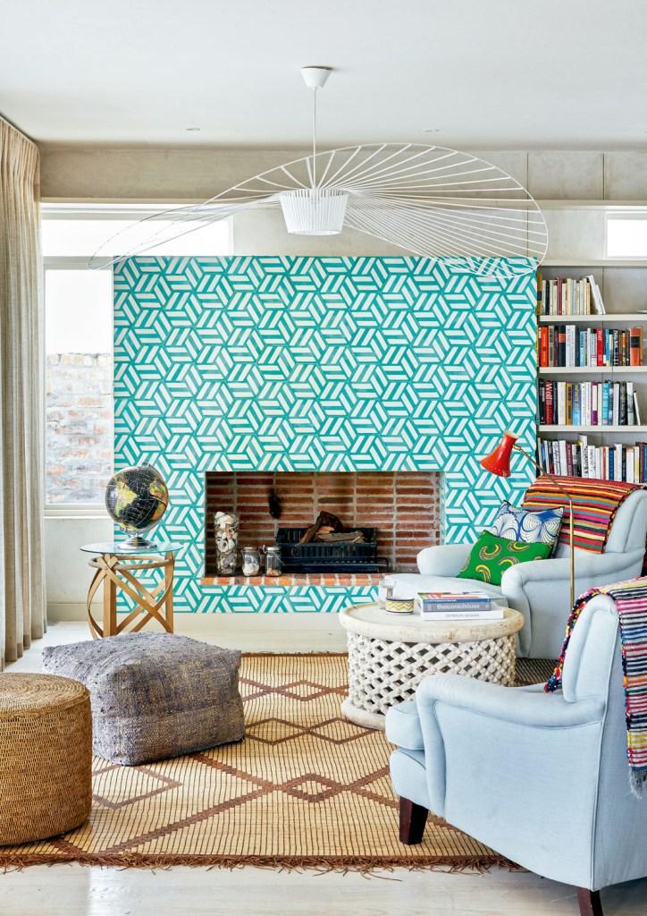 ambiente com lareira, estante com livros, poltronas e pufes