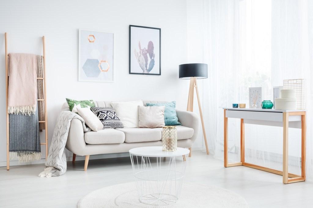 sala de estar com tons neutros, almofadas com estampas diferentes e dois quadros na parede