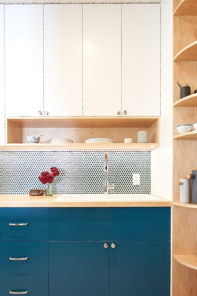 cozinha com armários inferiores azuis e superiores brancos, bancada da pia.