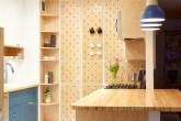 cozinha com parede com pegboards, três pendentes e bancada