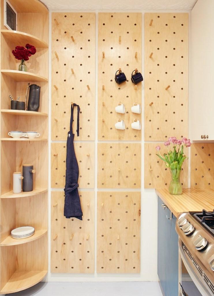 estante de madeira com objetos, parede com pegboards com xícaras penduradas