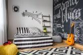 Quarto com decoração preta e branca, com cama listrada com um violão ao lado, tapete estampado. Notas musicais e um disco de vinil na parede atrás da cama. Parede de lousa com ritmos musicais escritos em giz.