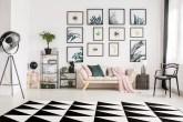 sala de paredes brancas com diversos quadros pendurados, tapete preto e branco e acessórios em cores claras