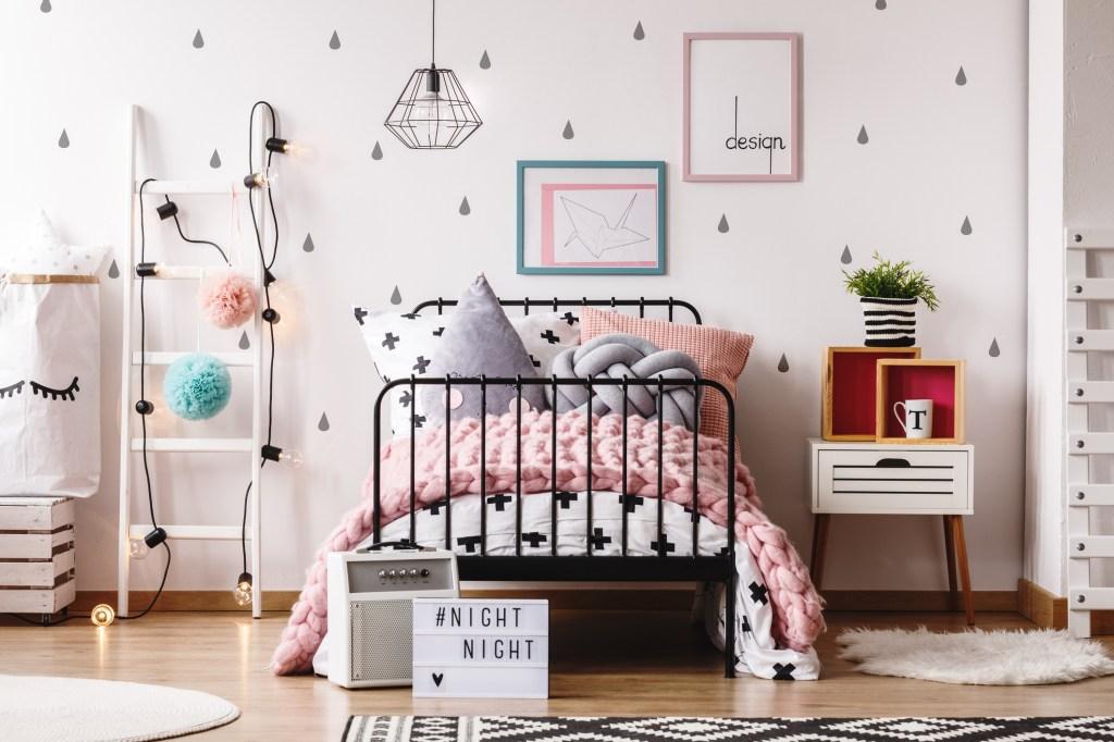 Quarto com papel de parede em formato de gotas, escada decorativa com luzes, quadros na parede e ambiente com paleta em tons pastel
