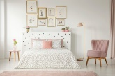 Quarto com paleta em tons de rosa e branco, cama com almofadas , quadros acima da cabeceira, poltrona e luminária e mesinha com um vaso de flor ao lado da cama.