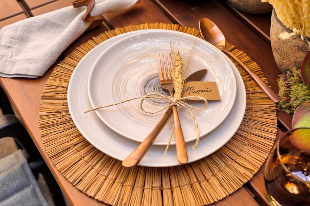jogo americano de palha com talheres dourados e um ramo de trigo