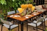 área externa com mesa posta e parede com plantas