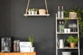 Cozinha com parede preta, escada como estante e prateleira suspensa por corda
