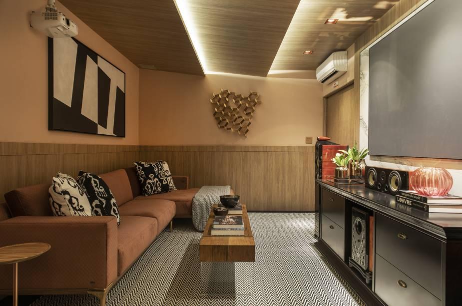 Sala de tv em tons terrosos com sofá laranja queimado e paredes laranja claro. Teto revestido em madeira. Hack preto.
