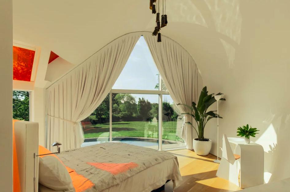 Quarto com janela para piscina. Cama de casal branca, escrivaninha e cortinas brancas. Vidro colorido laranja projeta sombra laranja na cama