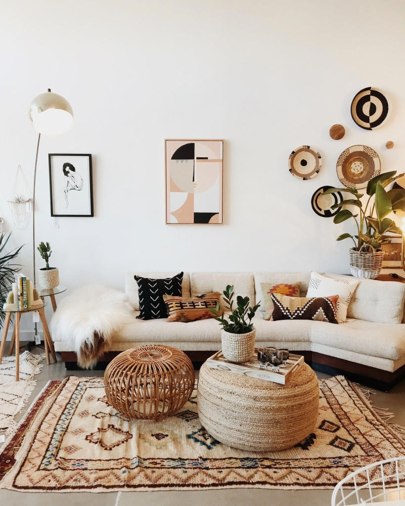 Sala em estilo boho com sofá e paredes branco, com quadros com estampa geométrica na parede, e tapete estampado no chão