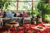 Decoraçnao estilo boho com tapete vermelho estamapado, sofá cinza com almofadas estampadas coloridas e muitas plantas