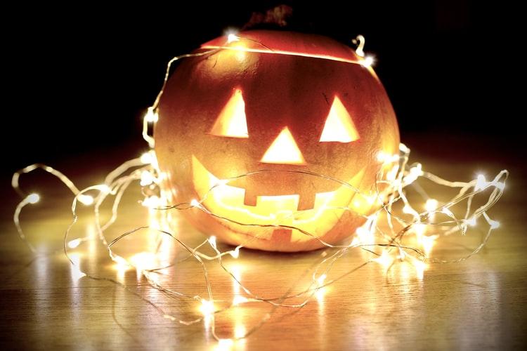 Abóbora cortada na temática de halloween e decorada com luzes