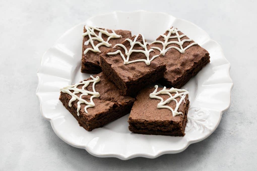 brownie de chocolate enfeitado com teias de aranha feitas de chocolate branco