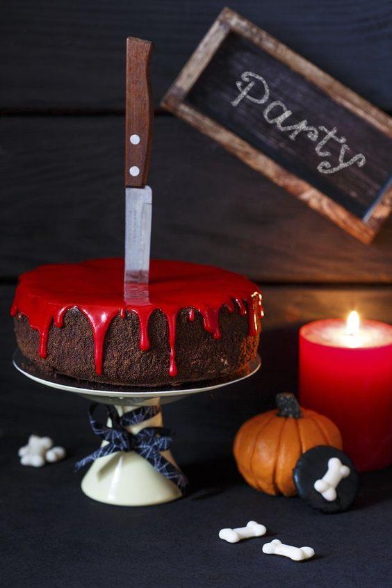 Bolo de chocolate com calda vermelha e uma faca em cima