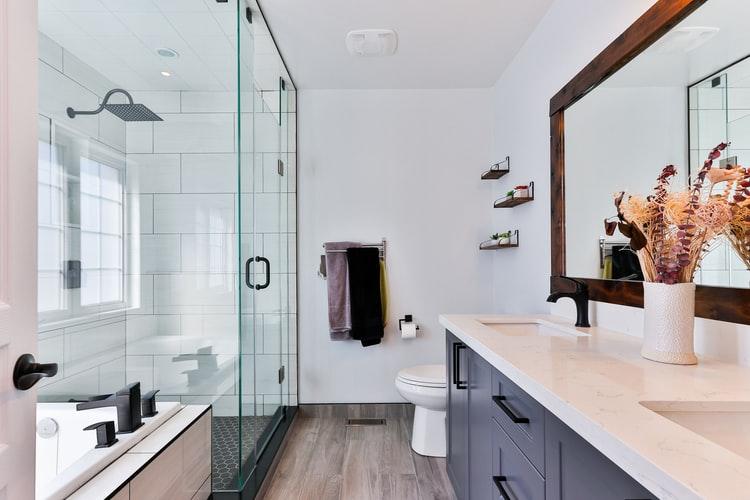 Banheiro amplo com box de vidro e bancada de madeira na cor azul