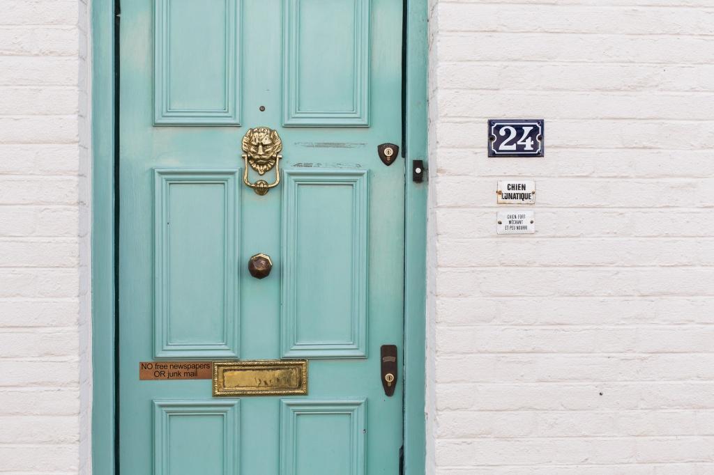 Fachada de uma casa com porta verde-água, parede de tijolinhos brancos e número 24