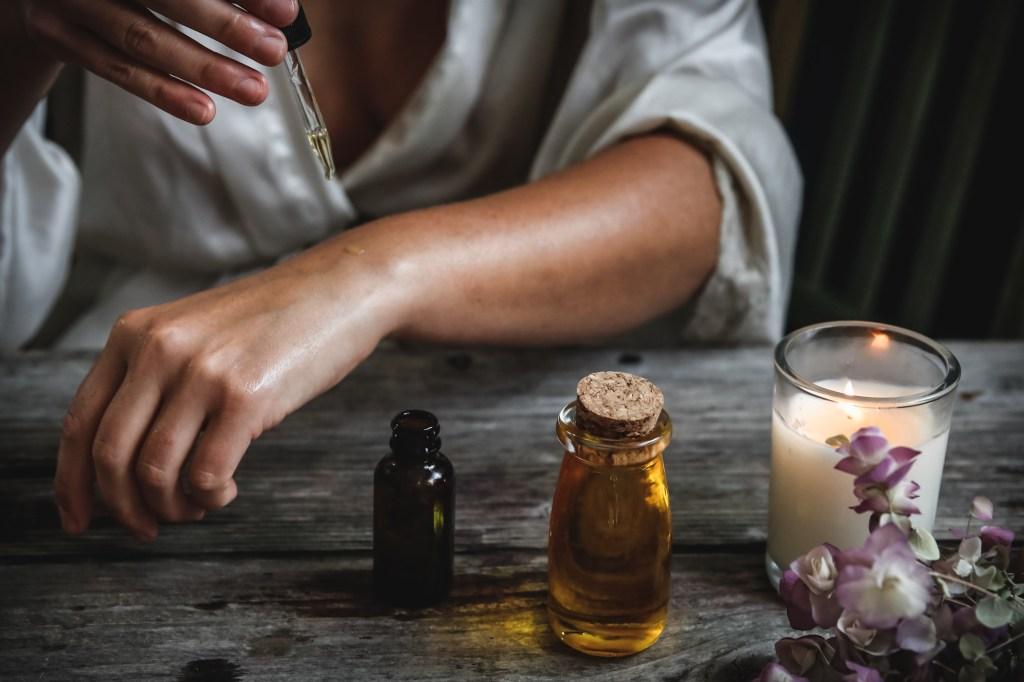Mulher passando óleo essencial no braço