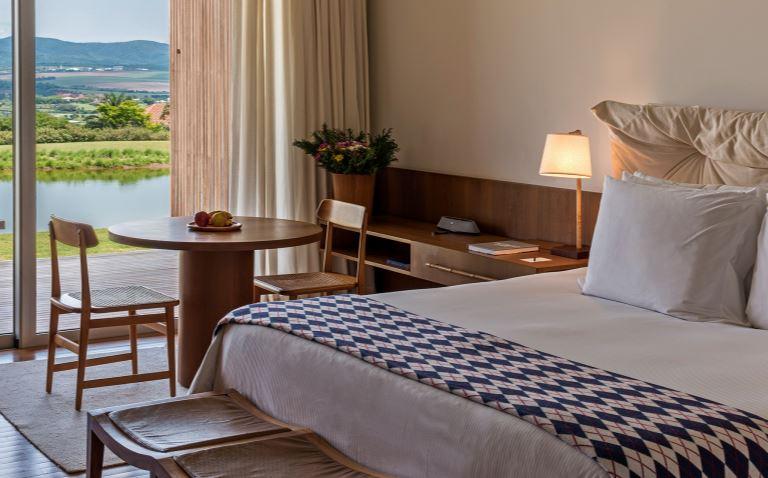 Quarto do hotel Fasano Boa Vista, com cama grande, mesa e duas cadeiras e vista para um lago e montanhas