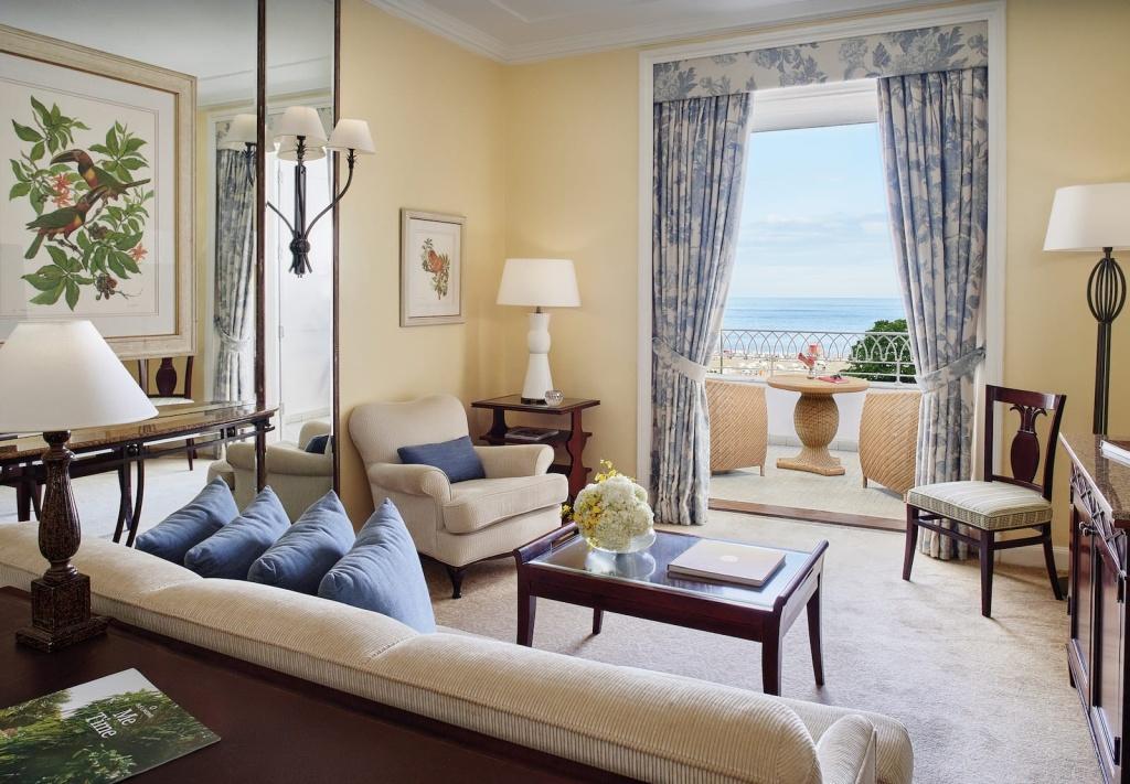 Sala de estar da suíte de um quarto com mesa e poltronas na sacada, do Belmond Copacabana Palace (RJ)