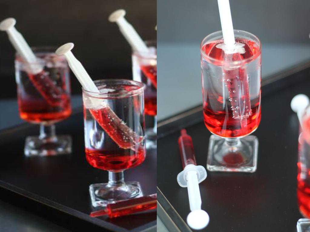 Copos com água com gás e seringa de plástico com líquido vermelho dentro