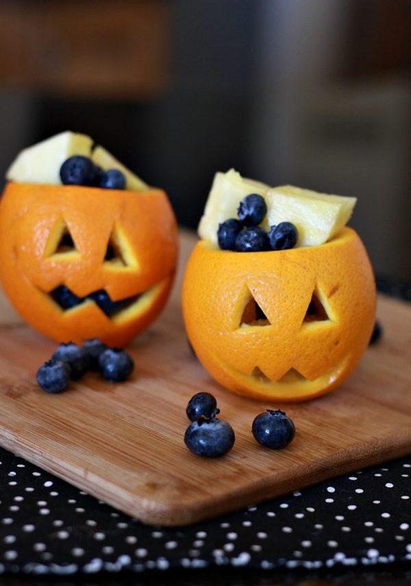 Laranja cortada em formato de abóbora e com blueberries e pedaços de abacaxi dentro