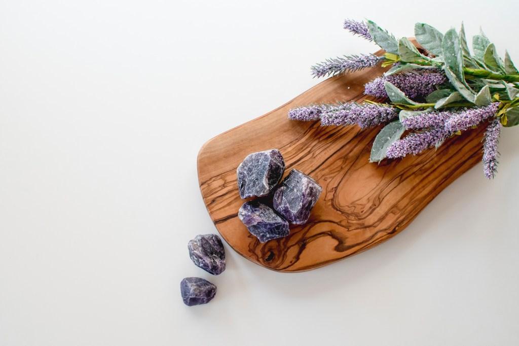 Buquê de lavanda e pedras na cor roxa sobre uma tábua de madeira