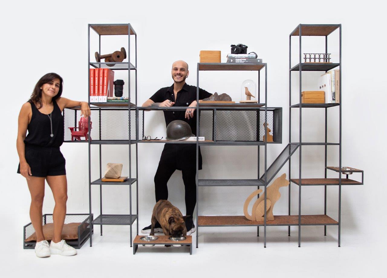 Acessórios de animais de estimação em estilo industrial criados pelos designers Pedro Galaso e Luciana Duque, que aparecem na imagem apoiados em uma estante modulada com objetos decorativos.
