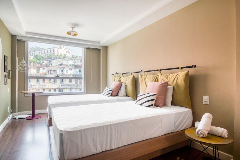 Quarto do Selina Lapa com duas camas, janela ampla, paredes, cabeceira e mesa de apoio na cor bege