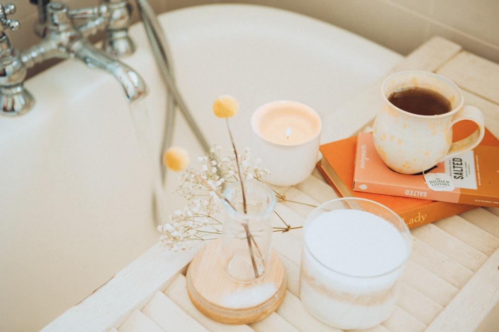 Velas, flores, livros e uma caneca de chá sobre um apoio de madeira em uma banheira de banho