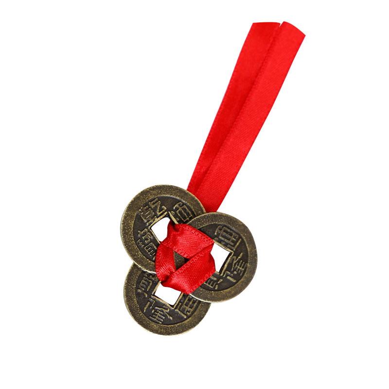 três moedas chinesas amarradas com uma fita vermelha