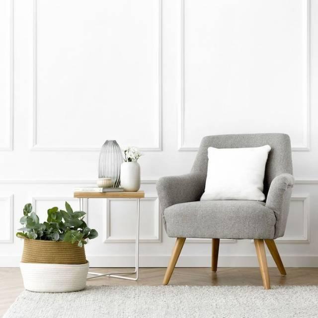 Poltrona cinza com almofada branca. Ao lado, uma mesa com um livro e vasinho com flores. No chão, um vaso branco em bege com uma planta