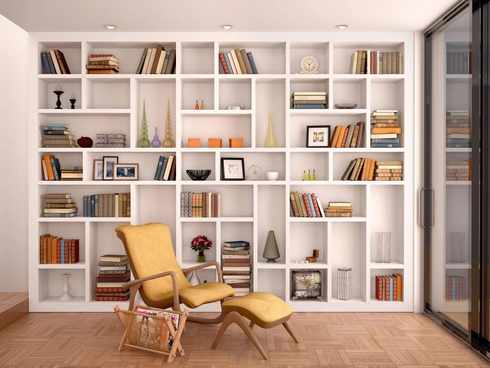 Estante branca com nichos. Nos nichos, livros, porta-retratos, vasos.