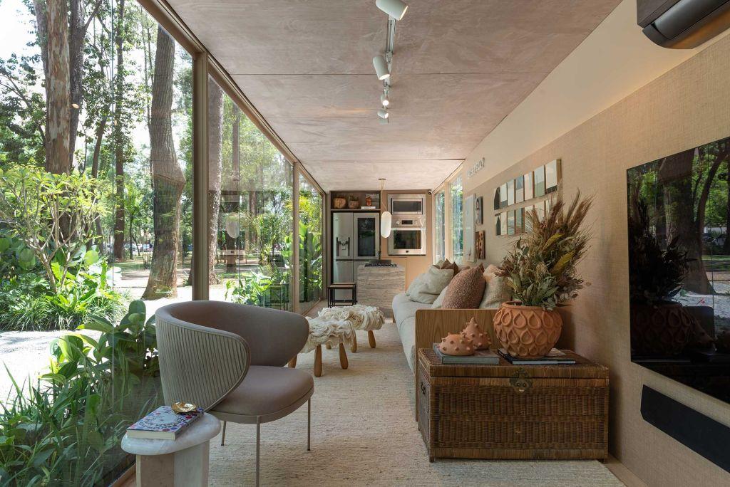 Casa Conectada LG do projeto Janelas CASACOR. Living com poltrona clara e televisão em primeiro plano. Ao fundo, sofá, pufes e cozinha equipada com geladeira forno e bancada