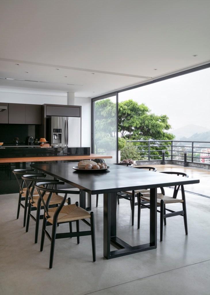 Espaço gourmet com mesa de jantar e cadeiras pretas